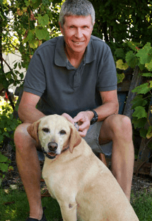 Dr. James Graham is an emergency medicine veterinarian. He is sitting next to a golden Labrador.