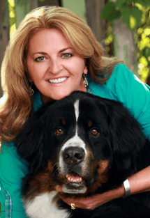 Dr. Lisa Peters is board certified in veterinary emergency and critical care medicine. She is hugging a large black and white dog.