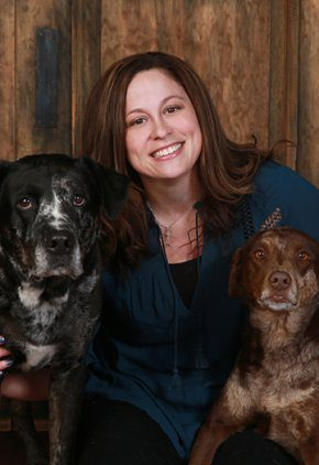 Dr. Samantha Vande Hey is an emergency medicine veterinarian. She is with two large black and brown dogs.