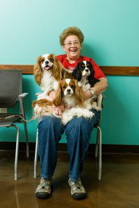 A smiling lady sits with three dogs on her lap.