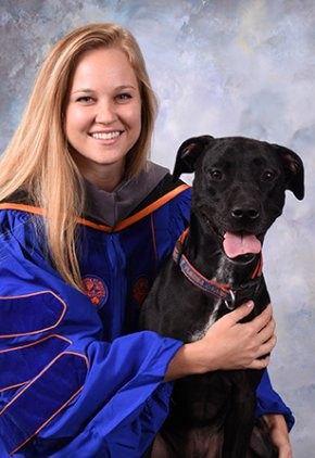 Dr. Riley Shugg is an emergency medicine veterinarian. She is holding a black dog.