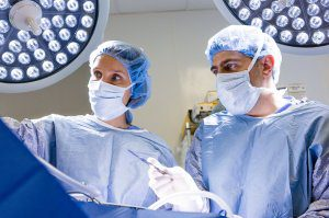 Two surgeons in blue gowns prepare to operate on a patient.