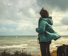 Woman stands staring at ocean with dog by her side.