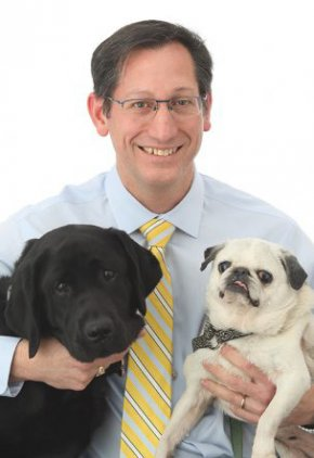 Dr. David Puerto is board certified in veterinary surgery. He is hugging a black dog and a pug.