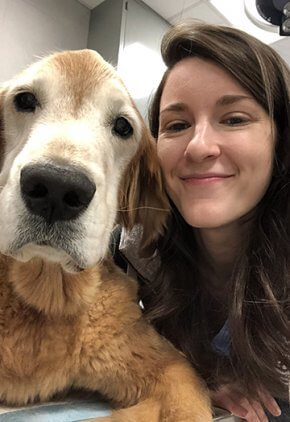Dr. Elisa McEntee is a veterinarian in our internal medicine service. She is next to a golden retriever.