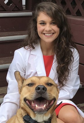 Dr. Kristen Clark is an emergency medicine veterinarian. She is with a brown dog.