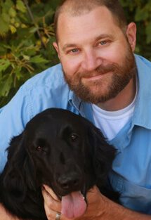Dr. Joseph Frank is board certified in small animal surgery. He has his arms around a black dog.