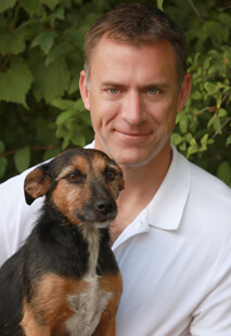 Dr. Bruce VanEnkevort is board certified in veterinary surgery. He is holding a small brown and black dog.