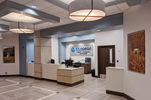 Bright, spacious lobby has large overhead lights and a desk.