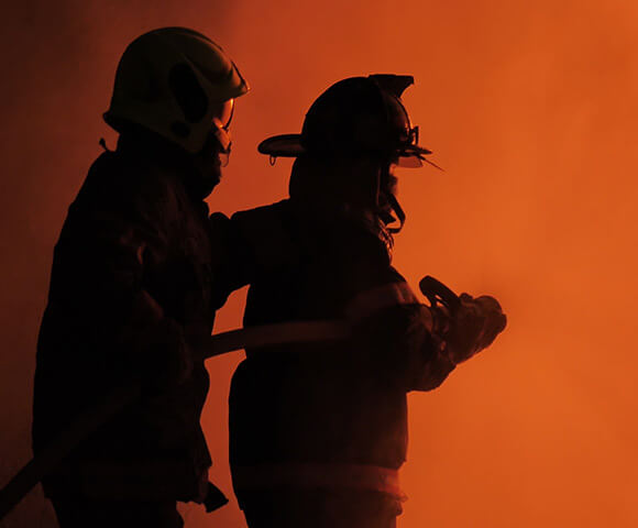 Two fire fighters walk through red hued smoke.