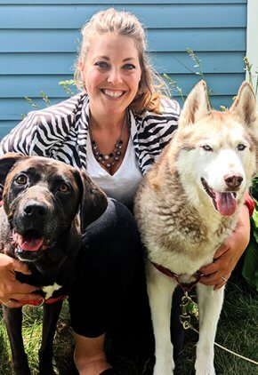 Dr. Natalie Morgan is a veterinarian in our cardiology service. She is sitting next to a brown dog and a husky.