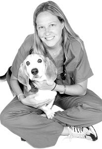 Dr. Suzanne Donahue is board certified in veterinary emergency & critical care. She is holding a beagle.