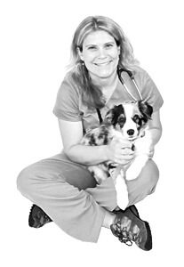 Dr. Sarah Muhrer is an emergency medicine veterinarian. She is sitting with a black and white dog.
