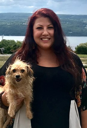 Dr. Laura Scoda is a veterinarian in our neurology service. She is holding a wire-haired brown dog.