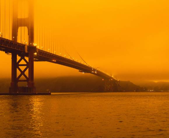 Golden gate bridge covered in orange smoke, resulting the California wildfires.