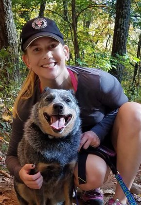 Dr. Elizabeth Golly is a veterinarian in our internal medicine service. She is on a nature trail with a brown and black dog.