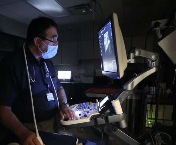 A veterinarian looks at a glowing screen in a dark room as he performs an ultrasound.