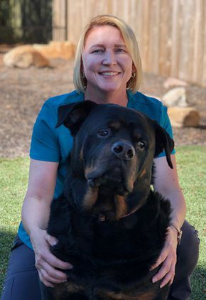 Dr. Dawn Johnson is an emergency medicine veterinarian. She is crouching and hugging a large black dog.