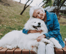 Older woman holds white fluffy dog while sitting on park bench.