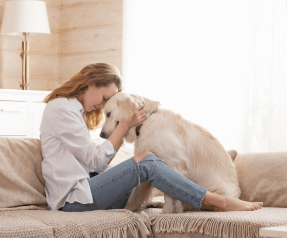 Woman holds Golden Retriever's head close to hers on couch, showing love and companionship.