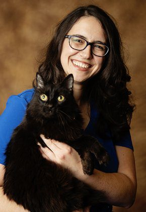 Dr. Rachel Lucia is an emergency medicine veterinarian. She is holding a black cat.