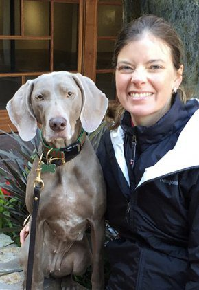 Dr. Grace Anne Mengel is an emergency medicine veterinarian. She is sitting with her arm around a Weimaraner.