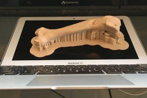 A 3d printed femur sits on a laptop screen for scale.