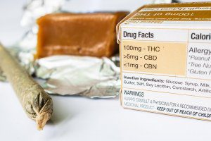A hand-rolled cigarette, box of medicine containing 100mg - THC, >5mg - CBD, <1mg - CBN; and a brick of tan solids rest on a table.