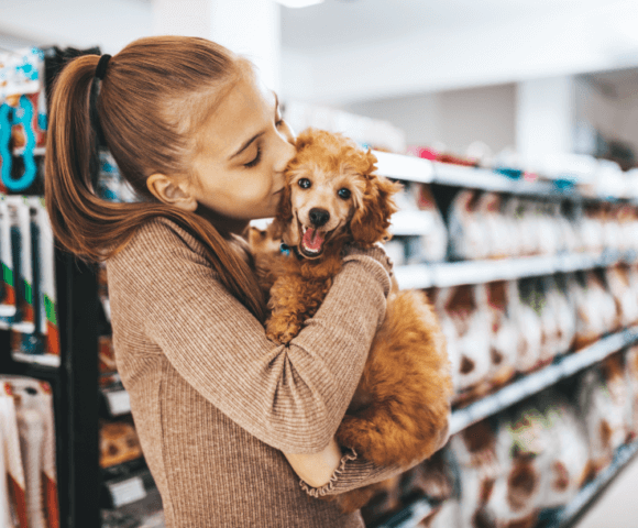Young girl kisses small dog on head in grocery store.