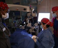 A surgeon performs cataract surgery with two techs nearby.