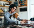 A young man with a beagle on his lap works on a laptop in his kitchen.