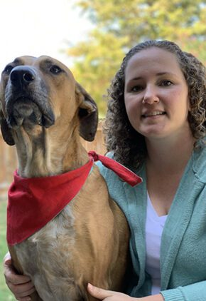 Dr. Jennifer Rizzo is an emergency medicine veterinarian. She is sitting next to a brown dog wearing a red bandana.