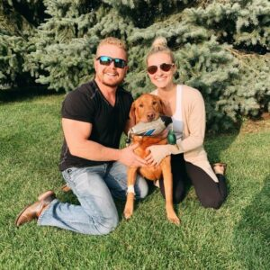Drake the red labrador retriever with his owners