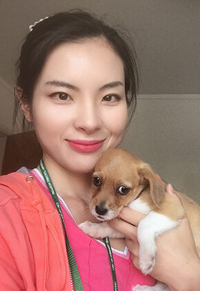Dr. Tingting Xia is a small animal medicine and surgery intern. She is holding a tan and white puppy.