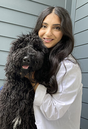 Dr. Merna Abdo is a small animal medicine and surgery intern. She is hugging a black doodle.