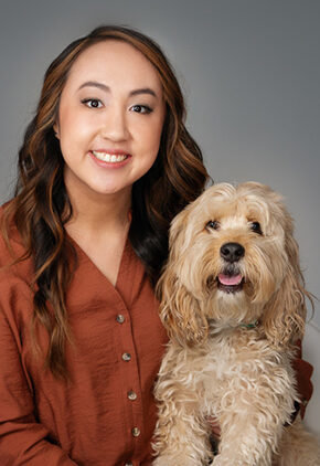 Dr. Rachel Wong is a small animal medicine and surgery intern. She is holding a tan dog.