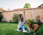 Woman plays with dog in backyard