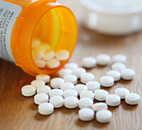 An orange pill bottle and white pills on a table