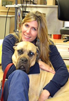 Dr. Allison Cornell is an emergency medicine veterinarian. She is on the floor with a large tan and black dog.
