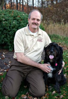 Dr. Anthony Pardo is board certified in veterinary surgery. He is outside with a large black dog.