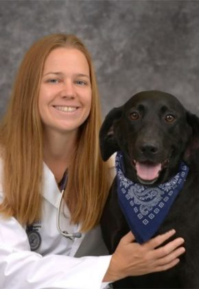 Dr. Jennifer Blouin is a clinician in our emergency medicine service. She is sitting next to a black dog wearing a blue bandana.
