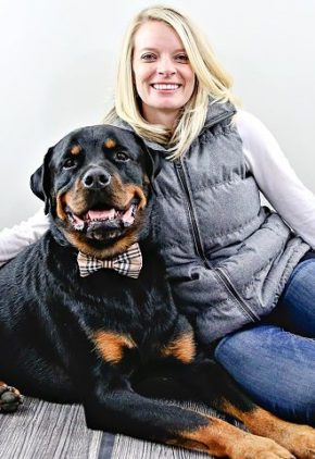 Dr. Carey Hemmelgarn is board certified in veterinary emergency and critical care medicine. She is sitting next to a Rottweiler wearing a bow tie.