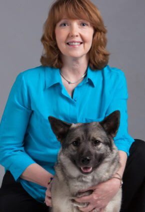 Dr. Connie Schulte is a veterinary rehabilitation practitioner. She is with a medium size black and gray dog.