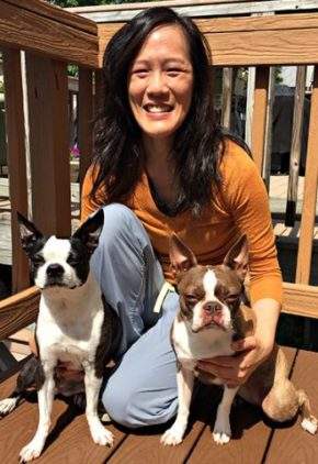 Dr. Wendy Kuo is an emergency medicine veterinarian. She is on a wooden deck with two Boston terriers.