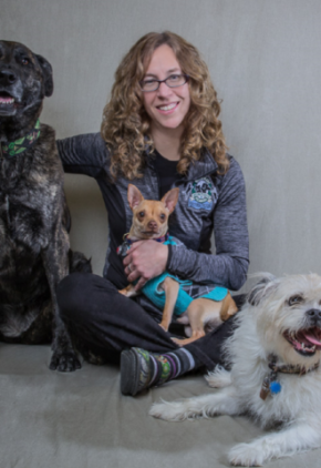 Dr. Natalie Campbell is certified in veterinary rehabilitation. She is sitting on the floor with three dogs.