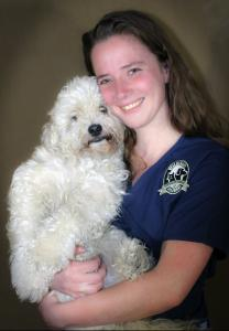 Dr. Brittany Gregory is a doctor in our emergency medicine service. She is holding a fluffy white dog in her arms.