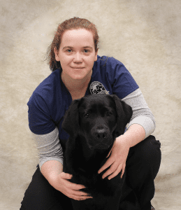 Dr. Lisa Murphy is board certified in veterinary emergency and critical care medicine. She is kneeling beside a black lab.