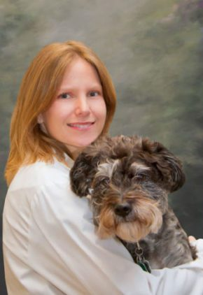 Dr. Ashley Davis is board certified in veterinary emergency and critical care medicine. She is hugging a long-haired dog.