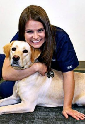 Dr. Catherine Strey is a veterinarian in our critical care service. She is hugging a yellow lab.