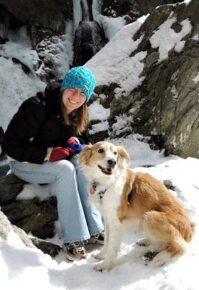 Dr. Kara Gornik is board certified in veterinary ophthalmology. She is in the snow with her tan and white dog.